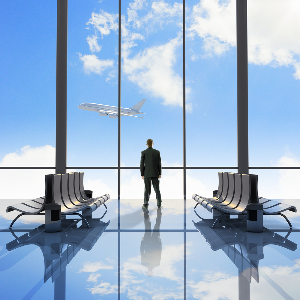 Businessman at airport looking at airplane taking off